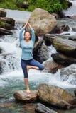 Donna nella posa dell'albero di Vrikshasana di asana di yoga alla cascata all'aperto Fotografie Stock