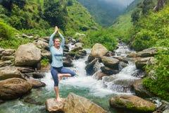 Donna nella posa dell'albero di Vrikshasana di asana di yoga alla cascata all'aperto fotografia stock