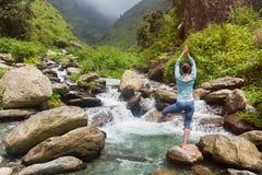 Donna nella posa dell'albero di Vrikshasana di asana di yoga alla cascata all'aperto immagini stock
