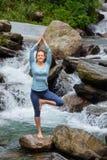 Donna nella posa dell'albero di Vrikshasana di asana di yoga alla cascata all'aperto immagini stock libere da diritti