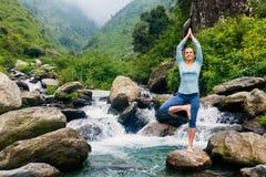 Donna nella posa dell'albero di Vrikshasana di asana di yoga alla cascata all'aperto immagine stock libera da diritti