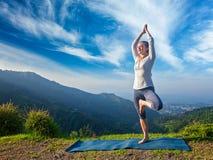 Donna nella posa dell'albero di Vrikshasana di yoga all'aperto fotografia stock
