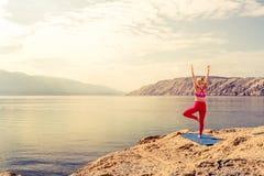 Donna nella posa dell'albero di yoga che medita al mare ed alle montagne Fotografia Stock Libera da Diritti