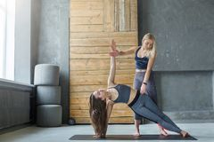 Donna nella posa della sponda con l'istruttore alla classe di yoga fotografia stock