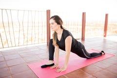 Donna nella posa di yoga del drago Immagine Stock