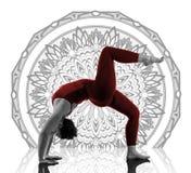 Donna nella posa di yoga di Urdhva Dhanurasana sul fondo della mandala Immagini Stock