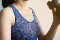 Donna nella scossa bevente della proteina degli abiti sportivi, sudore sulla pelle di abbronzatura H immagini stock