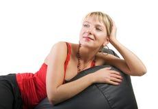 Donna nella stenditura rossa sul sofà Fotografia Stock