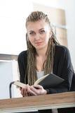 Donna nella sua cucina che legge un libro Immagine Stock