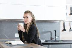 Donna nella sua cucina che legge un libro Immagini Stock Libere da Diritti