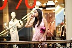 Donna nelle chiamate del negozio dal telefono fotografia stock libera da diritti
