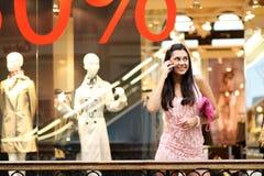 Donna nelle chiamate del negozio dal telefono immagine stock