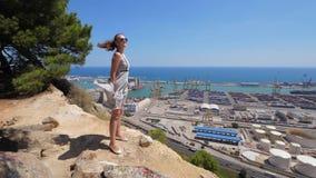 Donna nello sbattimento del vestito volante sulla cima della montagna, Barcellona stock footage