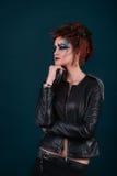 Donna nello stile scuro su un fondo blu Immagini Stock