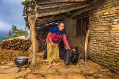 Donna nepalese anziana che prende cura della sua mucca nel Nepal Fotografia Stock Libera da Diritti