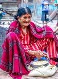 Donna nepalese molto anziana che vende i grani per i piccioni al tempio Immagini Stock