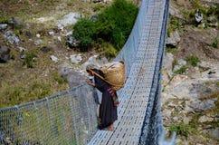Donna nepalese su un ponte Immagini Stock