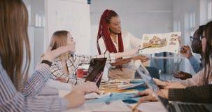 Donna nera professionale felice del responsabile di società di sviluppo che presenta progetto ai soci commerciali all'ufficio mod stock footage