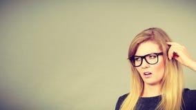 Donna nerd in occhiali che sono confusi fotografia stock