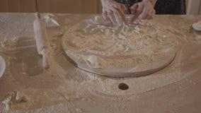 Donna non riconosciuta nel cuore di tiraggio del tavolo da cucina sul bordo della pasticceria con farina, matterello sulla tavola archivi video
