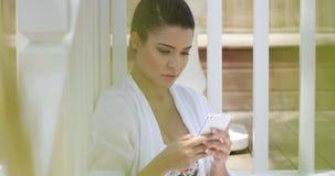 Donna non-sposata che si siede vicino al recinto facendo uso dello Smart Phone video d archivio