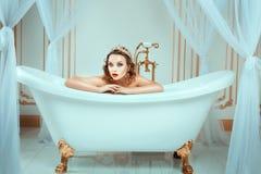 Donna nuda che si siede nel bagno costoso dei gioielli immagine stock