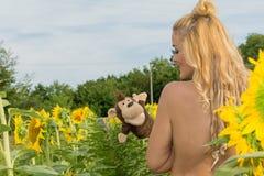 Donna nuda circondata dai girasoli Fotografia Stock Libera da Diritti