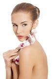 Donna nuda nuda che ha fiore bianco sulle spalle. Fotografia Stock