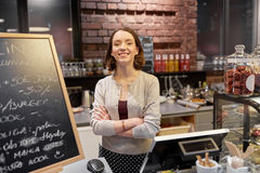 Donna o cameriera al banco felice al contatore del caffè Fotografia Stock