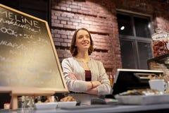 Donna o cameriera al banco felice al contatore del caffè Immagine Stock