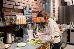 Donna o cameriera al banco felice che cucina al caffè del vegano Fotografie Stock Libere da Diritti