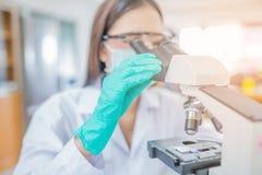Donna o chimico di medico che lavora con il microscopio Fotografie Stock