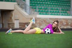 Donna o ragazza pon pon sexy di forma fisica con un pallone da calcio Fotografia Stock Libera da Diritti