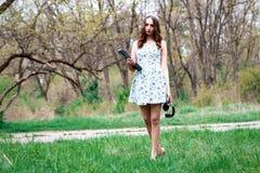 Donna o ragazza in un vestito, con il computer portatile e le cuffie felici in Th Fotografia Stock Libera da Diritti