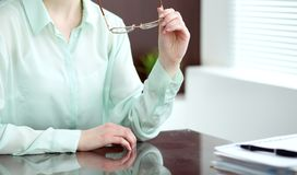 Donna o segretario di affari che si siede allo scrittorio nell'ufficio Il verde ha tonificato l'immagine Fotografia Stock Libera da Diritti
