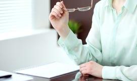 Donna o segretario di affari che si siede allo scrittorio nell'ufficio Il verde ha tonificato l'immagine Immagine Stock