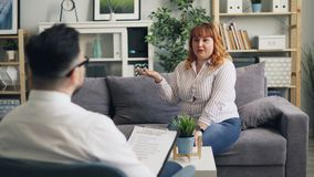 Donna obesa allegra che parla con psicologo maschio in clinica durante la sessione video d archivio