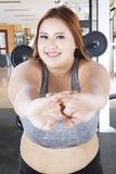 Donna obesa che allunga nel centro della palestra Fotografia Stock