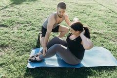 Donna obesa che fa sedere-UPS con l'istruttore personale fotografia stock libera da diritti