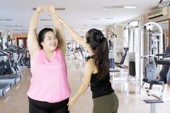 Donna obesa che fa un allenamento con il suo istruttore Fotografia Stock