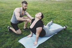 Donna obesa che fa yoga con il supporto dell'istruttore Fotografia Stock