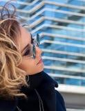 Donna in occhiali da sole con la riflessione di costruzione fatta di vetro Fotografie Stock