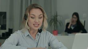 Donna occupata che ha conversazione importante tramite computer portatile nell'ufficio video d archivio