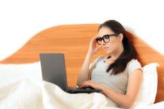 Donna occupata che lavora dalla casa sul suo computer portatile a letto Fotografie Stock
