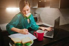 Donna occupata che mangia, caffè bevente, parlando sul telefono, lavorante ad un computer portatile allo stesso tempo Fare della  Fotografia Stock