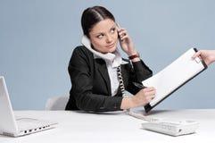 Donna occupata di affari che comunica dal telefono Immagine Stock
