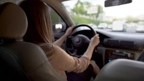 Donna occupata di affari che conduce automobile, affrettante alla conferenza trasporto video d archivio