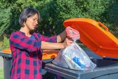 Donna olandese che getta immondizia di plastica nel recipiente di thrash Immagini Stock Libere da Diritti