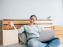 Donna online dell'imprenditore controllare le sue azione del prodotto in camera da letto immagine stock