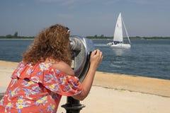 Donna osservando con binoculare a gettoni Immagini Stock Libere da Diritti